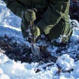 Le soldat du génie se mettant à genoux au sol couvert de neige creuse image stock