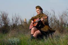 Le soldat féminin soviétique dans l'uniforme de la deuxième guerre mondiale joue la guitare Image stock