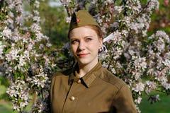 Le soldat féminin soviétique dans l'uniforme de la deuxième guerre mondiale se tient près de l'arbre fleurissant photos libres de droits