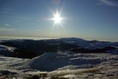 Le soleil brillant au-dessus des montagnes Photo libre de droits