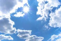 Le soleil brillant parmi le ciel bleu Photo stock