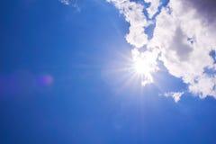 Le soleil brillant réaliste avec la fusée de lentille Ciel bleu avec des nuages Photos libres de droits