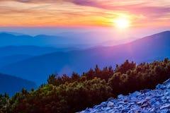Le soleil coloré de coucher du soleil opacifie et au-dessus des montagnes bleues Photographie stock libre de droits