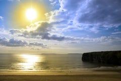 Le soleil d'or au-dessus de la plage et des falaises de Ballybunion Photographie stock libre de droits