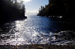 Le soleil d'hiver miroite sur les eaux bleues d'une petite baie photo stock