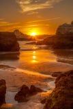 Le soleil d'or marche vers le bas à la plage entre les roches Photos stock