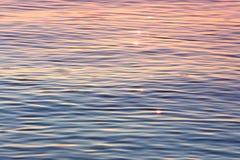 Le soleil de début de soirée miroitant sur l'eau calme Images libres de droits