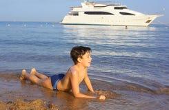 Le soleil de la préadolescence beau a bronzé la natation de garçon sur la plage de mer de recherche Images stock