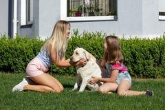 Le soleil de maison de parc d'été d'herbe d'animal familier de fille de mère de chien de Labrador riant l'été blond de nourrisson Photos libres de droits