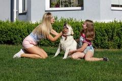 Le soleil de maison de parc d'été d'herbe d'animal familier de fille de mère de chien de Labrador riant l'été blond de nourrisson Photos stock