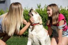 Le soleil de maison de parc d'été d'herbe d'animal familier de fille de mère de chien de Labrador riant l'été blond de nourrisson Images libres de droits