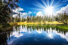 Le soleil de matin est reflété dans l'eau lisse du lac Image libre de droits