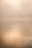 Le soleil de matin par le brouillard au lac Image stock