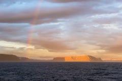 Le soleil de milieu de l'été et arc-en-ciel, Islande Image libre de droits