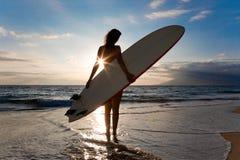 Le soleil de planche de surfing de femme photographie stock libre de droits