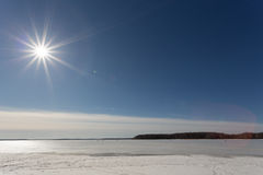 Le soleil de ressort pendant l'après-midi au-dessus du lac couvert de la glace Images stock