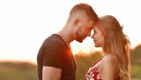 Le soleil de soirée illumine de jeunes couples étreignant sur le champ Photographie stock libre de droits