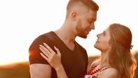 Le soleil de soirée illumine de jeunes couples étreignant sur le champ Image libre de droits