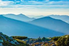 Le soleil de soirée rayonne parmi des silhouettes de montagne au coucher du soleil Photo libre de droits