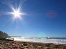 Le soleil de Starburst évase au-dessus de la plage de Warriewood Photographie stock libre de droits
