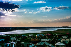 Le soleil derrière les nuages sur un ciel bleu au-dessus de la baie et des dessus de toit de ville Images libres de droits
