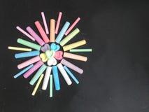 Le soleil des crayons sur un fond noir Photo stock