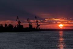 Le soleil ensanglanté descend dans l'eau par les nuages Image libre de droits