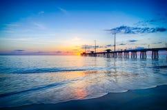 Le Soleil Levant jette un coup d'oeil par des nuages et est reflété dans les vagues par Photos stock