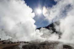 Le Soleil Levant lumineux au-dessus d'éclater le geyser chaud de la vapeur en geysers d'EL Tatio mettent en place au lever de sol photo stock