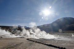 Le Soleil Levant lumineux au-dessus d'éclater le geyser chaud de la vapeur en geysers d'EL Tatio mettent en place au lever de sol photo libre de droits