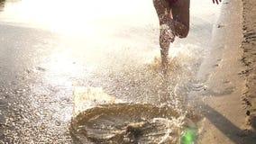 Le soleil lumineux éclabousse de la mouche de l'eau dans différentes directions Mouvement lent La fille court nu-pieds le long du banque de vidéos