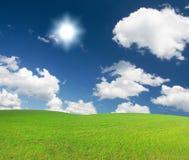 le soleil nuageux bleu de ciel de côte verte sous le petit morceau Photos stock