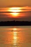Le soleil partiellement caché d'or de coucher du soleil de lac nuageux Images libres de droits