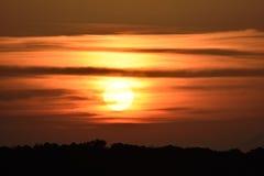 Le soleil partiellement caché nuageux d'or de coucher du soleil Images libres de droits