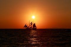 Le soleil plaçant au-dessus d'un bateau de navigation dans Santorini Photo stock