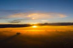 Le soleil plonge dans une masse énorme des nuages avant de descendre photographie stock