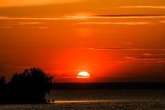 Le soleil rouge place au-dessus de l'eau et de la forêt Photos stock