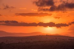 Le soleil rougeoie derrière les nuages pourpres dans un ciel intense de rouge orange image libre de droits