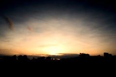 Le soleil se lève au-dessus des cimes d'arbre pendant le matin images libres de droits