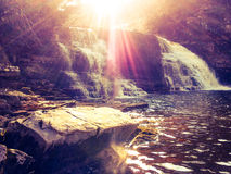 Le soleil sur une belle cascade Photographie stock