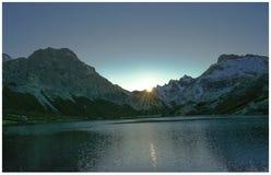 Le soleil tombe derrière les montagnes images stock