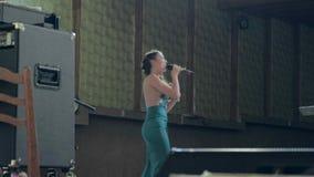 Le soliste féminin d'un groupe de rock musical exécute avec émotion une chanson pendant un concert, dans le guitariste de fond, i clips vidéos