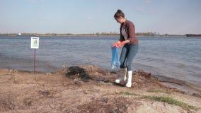 Le soluzioni ambientali, volontario della ragazza raccoglie i rifiuti di plastica nella borsa di immondizia e dà il gesto positiv video d archivio