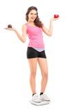 Le som är kvinnligt på ett vägafjällinnehav ett röd äpple och tårta Royaltyfria Bilder