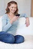 Le som är kvinnligt surfa rengöringsduken med henne smartphone på sofaen royaltyfria bilder
