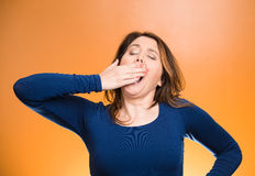 Le sommeil a privé la jeune femme plaçant la main sur la bouche baîllant Image stock