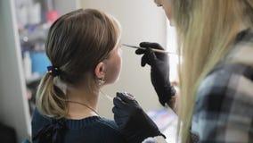 Le sopracciglia del disegno del truccatore ad una ragazza graziosa con una spazzola professionale davanti ad uno specchio in un s archivi video