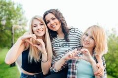 Le sorelle adulte in un parco al giorno meraviglioso che fa il cuore gesture fotografie stock