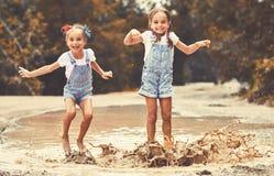 Le sorelle divertenti felici gemella il bambino dalla ragazza che salta sulle pozze e sulla risata Fotografie Stock