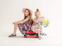 Le sorelle felici stanno sedendo su una valigia Fotografie Stock